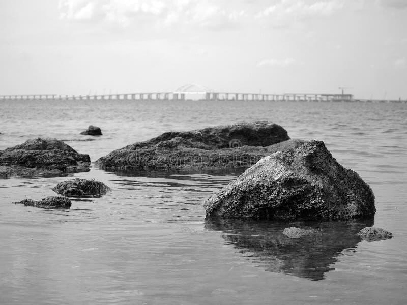 Mer, roches, pont à l'arrière-plan La photographie noire et blanche souligne le contraste entre la pierre et l'eau photo libre de droits