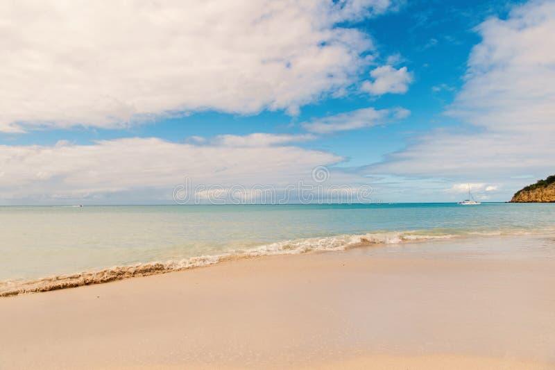 Mer tropicale de bleu de vague de plage de sable idyllique de sc?ne Chacun devrait visiter les stjohns tropicaux Antigua de stati photo libre de droits
