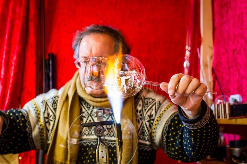 Merano, Tirol sul, Itália - 16 de dezembro de 2017: Um homem está fazendo as bolas de vidro do Natal no mercado do Natal de Meran imagens de stock royalty free