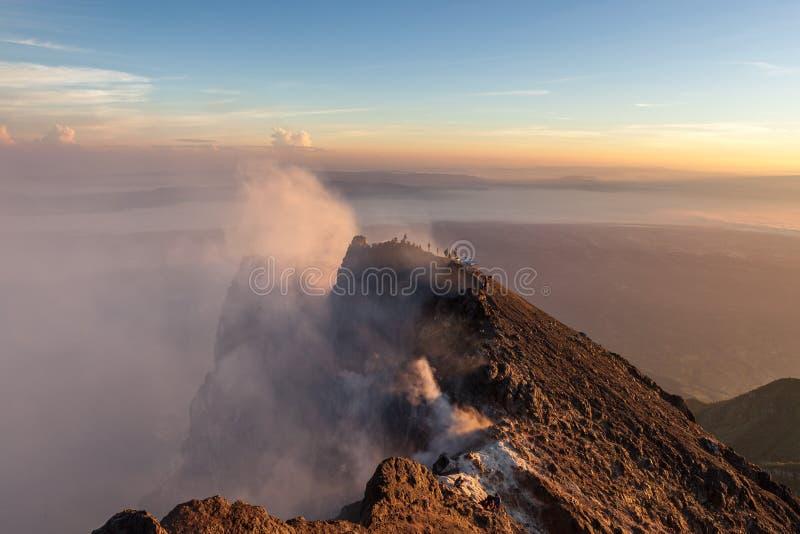 Merapi火山与爬上的人的火山口外缘 库存图片
