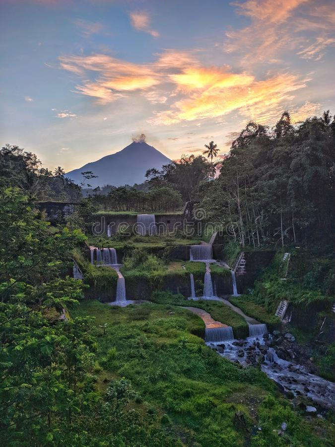 Merapi mountain view from Mangunsuko bridge, Magelang Indonesia. Sunrise with forest scenery, dam and Mountain royalty free stock image