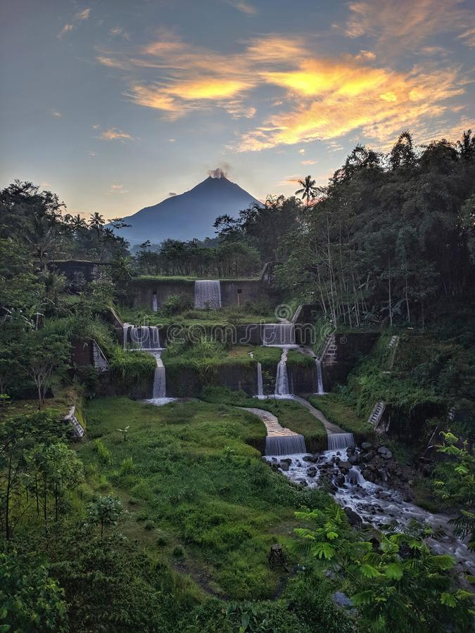 Merapi mountain view from Mangunsuko bridge, Magelang Indonesia. Sunrise with forest scenery, dam and Mountain royalty free stock images
