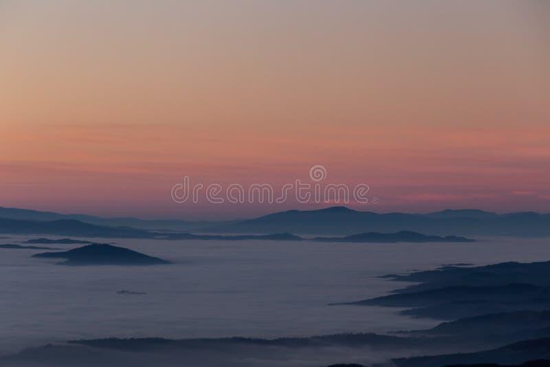 Meravigliosamente ha colorato il cielo al crepuscolo, con gli strati delle montagne sopra un mare di nebbia immagine stock