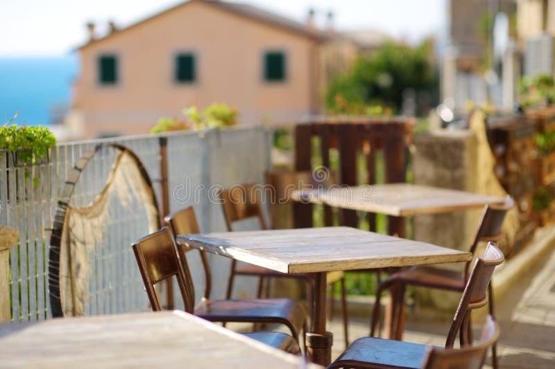 Meravigliosamente ha decorato le piccole tavole all'aperto del ristorante nel villaggio di Riomaggiore, Cinque Terre, Italia immagini stock