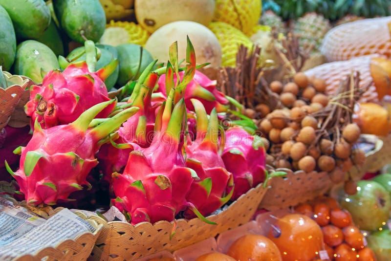 Mercado asiático de la comida del concepto La fruta Pitahaya del dragón y el dragón observan el Longan en el vendedor contrario d imagen de archivo