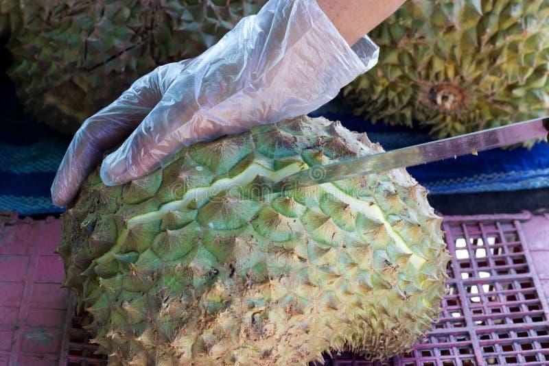 Mercado de la comida de Phuket, Tailandia: el vendedor corta el durian fresco con el cuchillo fotografía de archivo