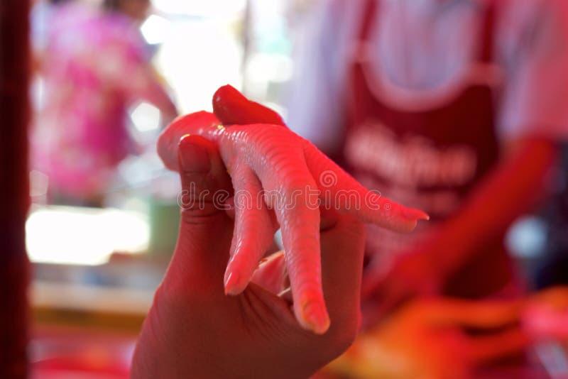 Mercado de la comida de Phuket, Tailandia: mano que lleva a cabo el pie crudo del ` s del pollo imagen de archivo libre de regalías