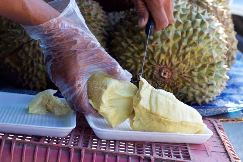 Mercado de la comida de Phuket, Tailandia: vendedor que corta el pedazo de durian fresco imagen de archivo libre de regalías