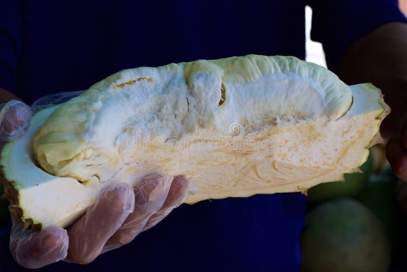 Mercado de la comida de Phuket, Tailandia: vendedor que lleva a cabo el pedazo de durian fresco imagen de archivo