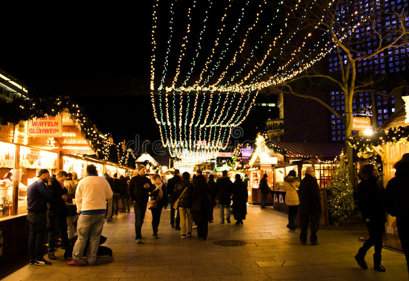 Mercado Defocused do Natal de Berlim na noite Povos que comem e que andam através do mercado de rua decorado imagens de stock royalty free