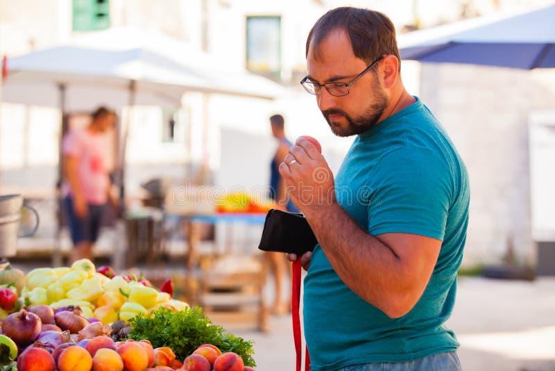 Mercado externo de produtos hortícolas e cliente do sexo masculino fotografia de stock