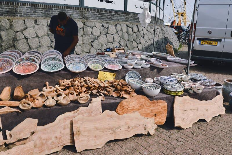 Mercado portuário de sexta-feira em Oudeschild, com dois a vender produtos feitos de madeira derivada e de dinnerware colorido imagens de stock