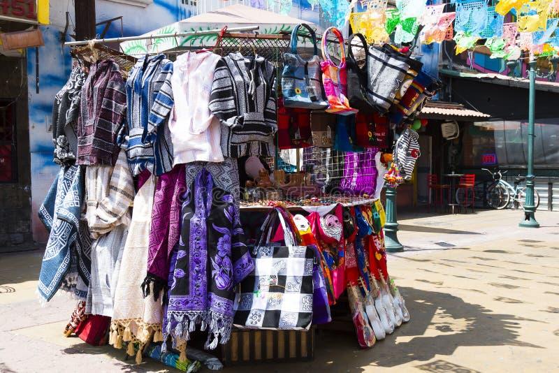 Mercancía del vendedor en el soporte en la plaza Santa Cecilia en Tijuana, México fotos de archivo