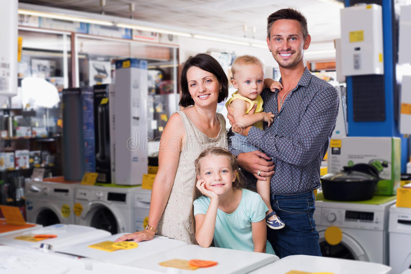 Mercancías que hacen compras de la familia de cuatro miembros feliz en hogar imagen de archivo libre de regalías