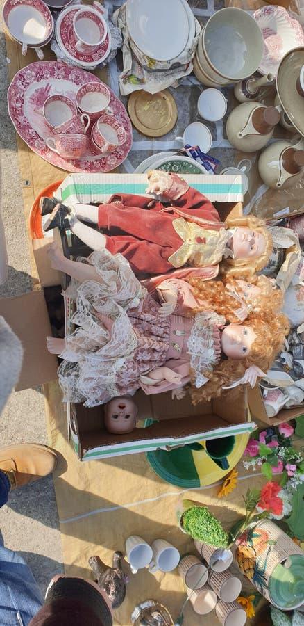 Mercato delle pulci in bambole d'annata della Romania di timisoara e giocattoli e tazza da the chabbychic per tè fotografie stock libere da diritti