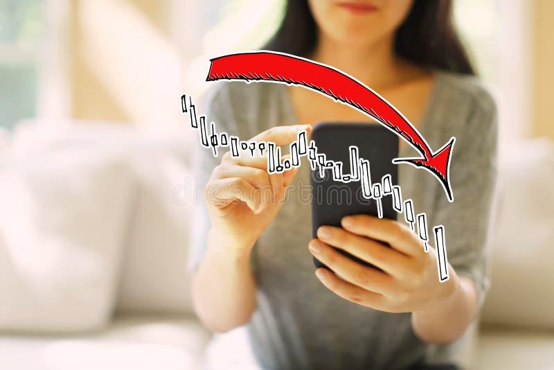 Mercato giù il grafico di tendenza con la donna che per mezzo di uno smartphone fotografia stock