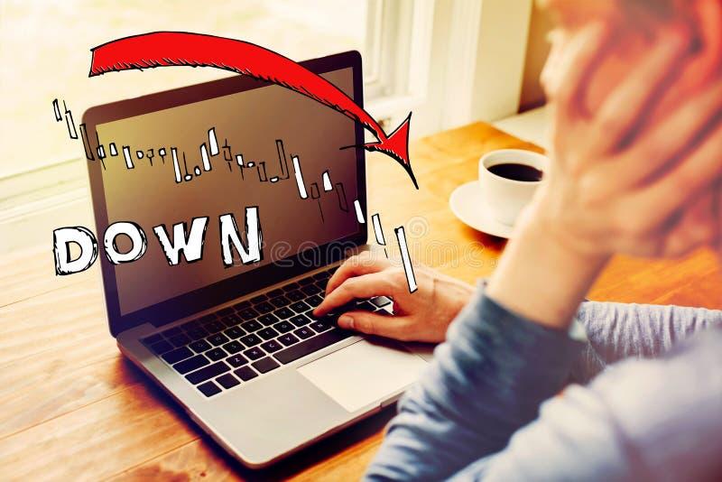 Mercato gi? il grafico di tendenza con l'uomo facendo uso di un computer portatile immagine stock