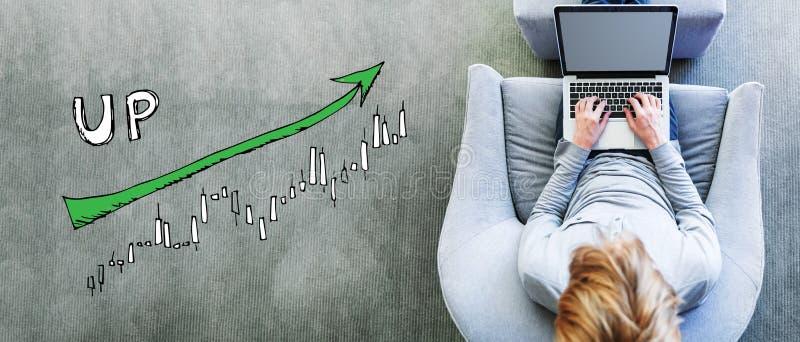 Mercato sul grafico di tendenza con l'uomo facendo uso di un computer portatile immagini stock libere da diritti