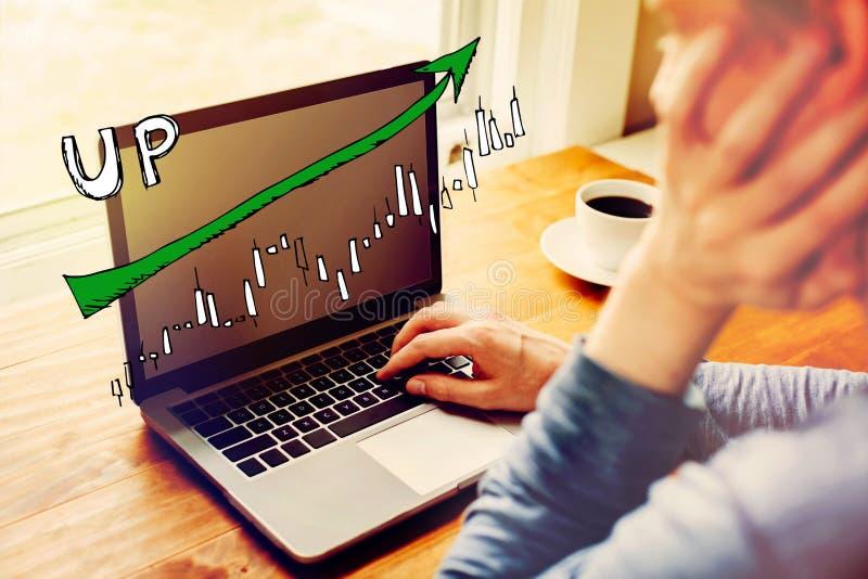 Mercato sul grafico di tendenza con l'uomo facendo uso di un computer portatile immagine stock
