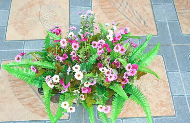 Merce nel carrello dei fiori artificiali sul pavimento immagini stock libere da diritti