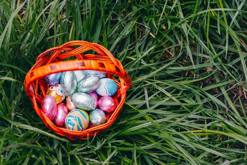 Merce nel carrello delle uova di Pasqua del cioccolato sul fondo dell'erba verde immagine stock
