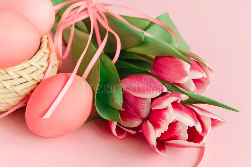 Merce nel carrello delle uova di Pasqua su fondo rosa pastello decorato con i tulipani Cartolina d'auguri immagine stock