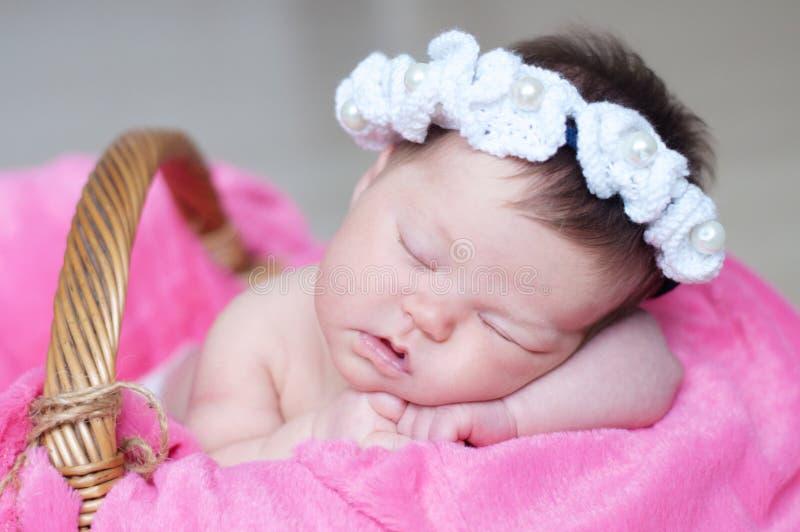 Merce nel carrello infantile di sonno con l'accessorio - banda capa, neonata che si trova sulla coperta rosa, bambino sveglio, ne immagine stock