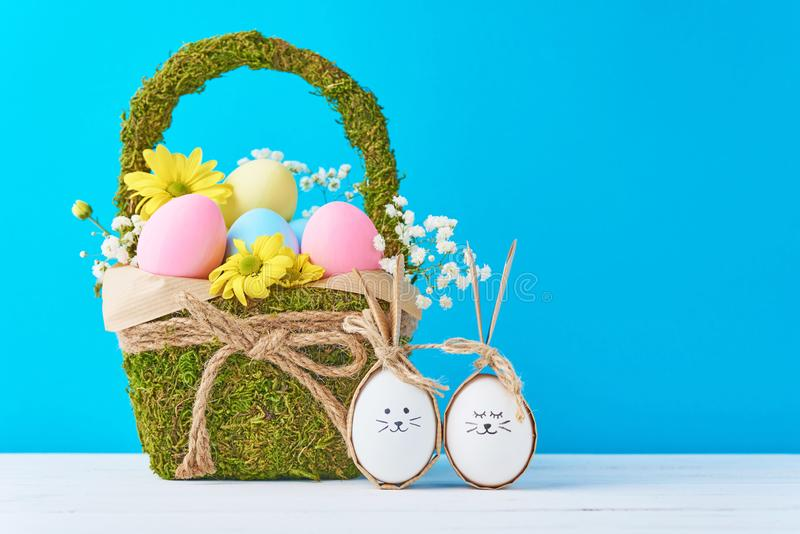 Merce nel carrello variopinta delle uova di Pasqua con le decorazioni dei fiori su un fondo blu fotografia stock libera da diritti
