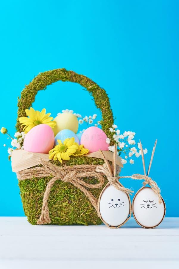 Merce nel carrello variopinta delle uova di Pasqua con le decorazioni dei fiori su un fondo blu fotografie stock libere da diritti