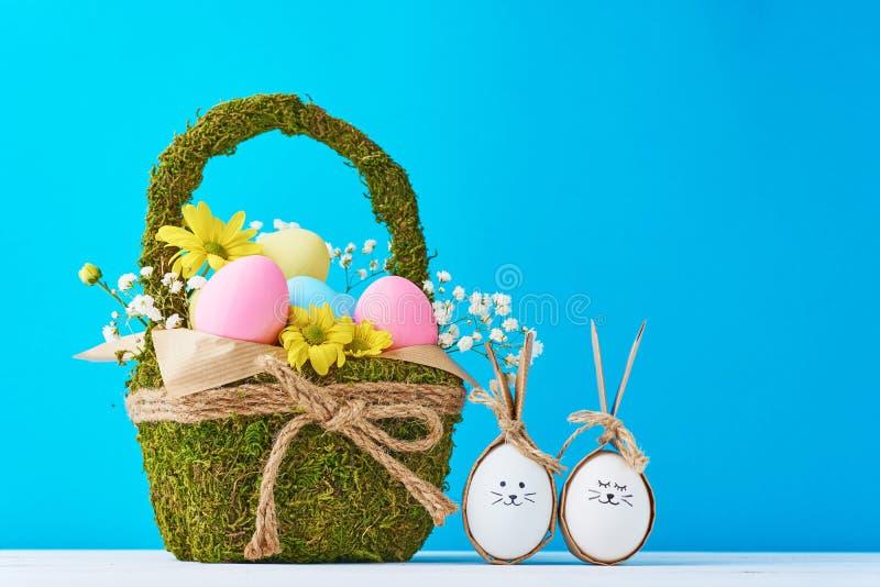 Merce nel carrello variopinta delle uova di Pasqua con le decorazioni dei fiori su un fondo blu fotografie stock