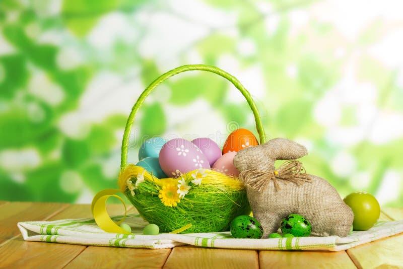 Merce nel carrello variopinta delle uova di Pasqua e coniglietto di pasqua, caramella, nastro fotografia stock