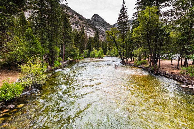 Merced flod som flödar till och med den Yosemite dalen, Yosemite nationalpark, Kalifornien; molnig sommardag royaltyfri foto
