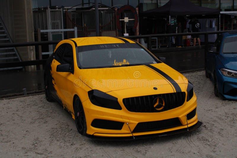 Yellow black Mercedes, power, rain  royalty free stock image