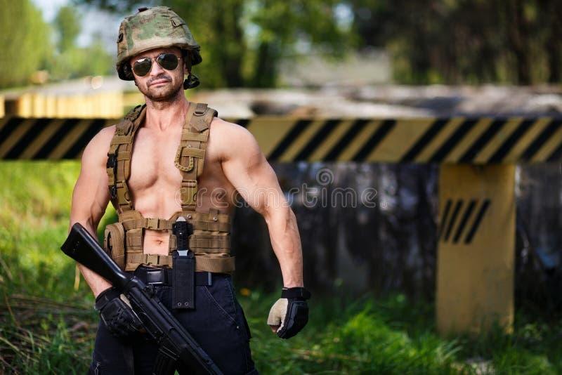 Mercenaire puissant avec la mitraillette gardant un barrage de route photo libre de droits