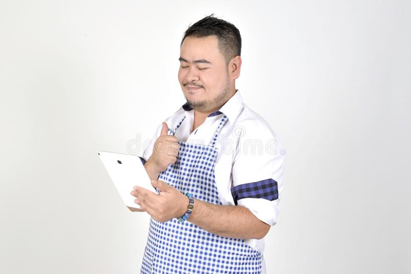 Merchant Asian man in white and blue apron is feeling surprised or excited when get good news from connection internet in tablet royalty free stock images