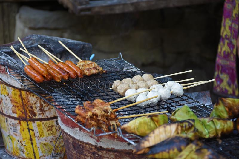 Merchant are grilled meet ball and meet stick on street road.  stock photos