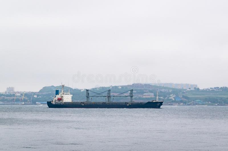 A merchant ship leaves its home port. A merchant ship leaves Vladivostok across Zolotoy Rog bay on the background of the urban landscape its home port stock photo