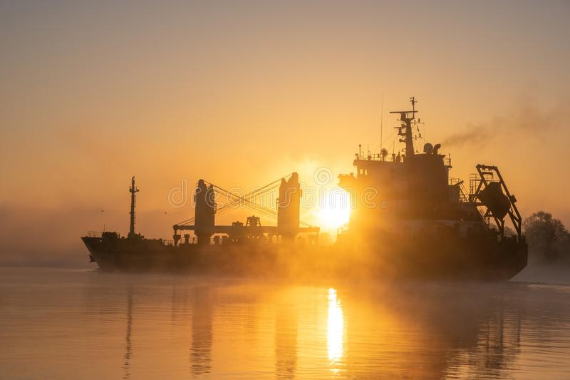 Merchant ship sailing down the river. In the mist at sunrise stock photos