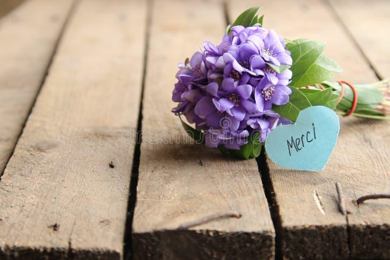 Merci escrito en etiqueta y las flores imagen de archivo libre de regalías