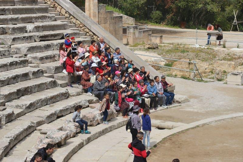 MERCI le groupe de touristes asiatiques écoute un guide Sur les escaliers du théâtre antique d'Epidauros, Péloponnèse, Grèce, photos stock