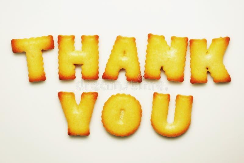 Merci mot des biscuits d'alphabet sur le fond blanc images stock