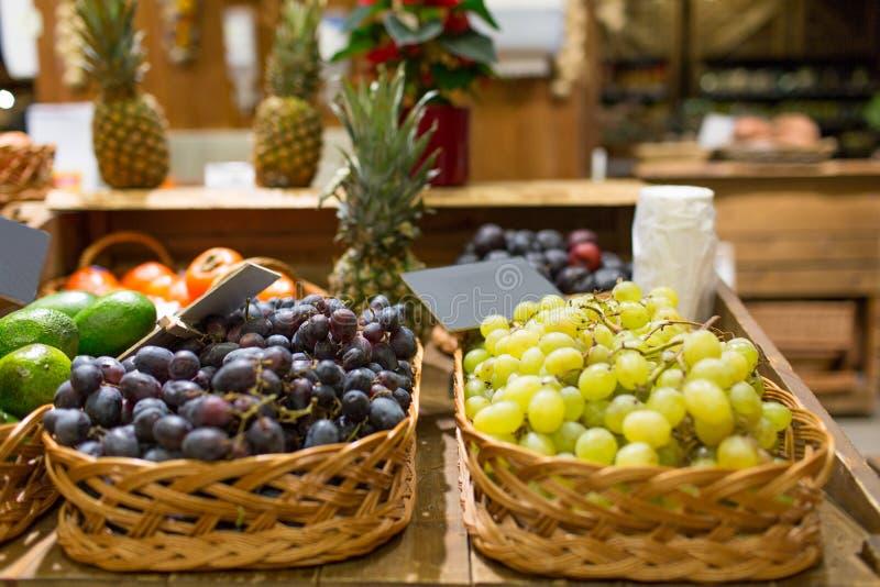 Merci nel carrello dell'uva con le targhette al mercato dell'alimento fotografie stock libere da diritti