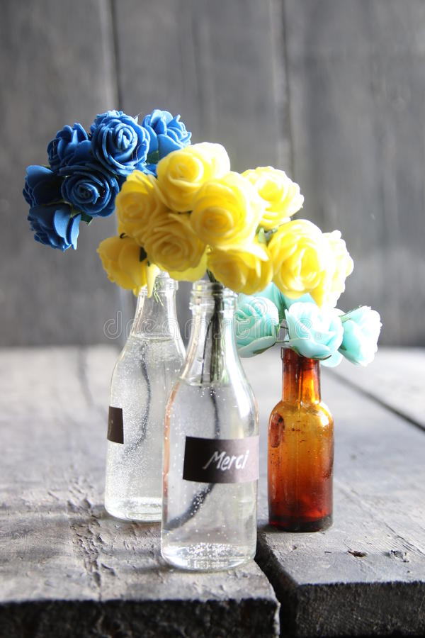 Merci tag and nice flowers in the bottles. Nice flowers in the bottles and label Merci, vintage style royalty free stock images