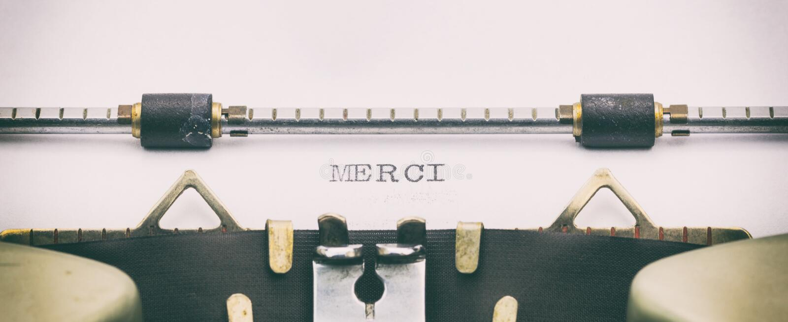 Merci word in capital letters on a typewriter sheet royalty free stock photo