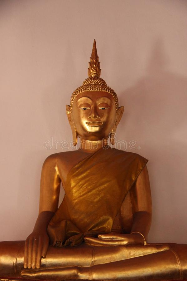 merciful Buda dourada de sorriso da cara no templo budista imagem de stock