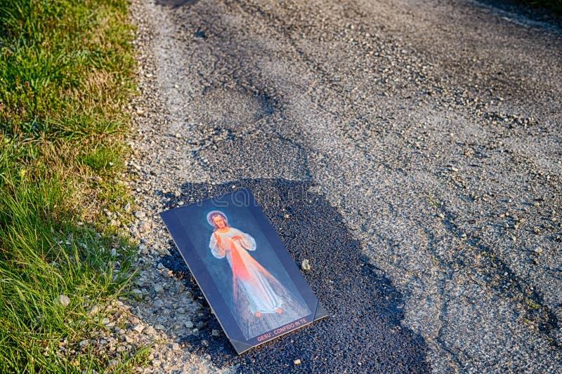 Merciful Jesus icon on dirt asphalt road stock image