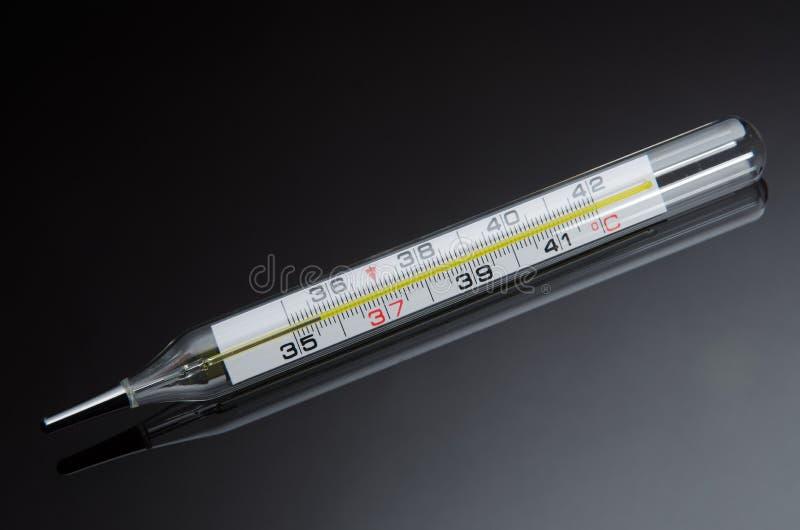 Mercury dans le thermomètre en verre sur le fond noir avec la réflexion photo libre de droits