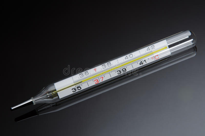 Mercury in glass thermometer on black background with reflection royalty free stock photo