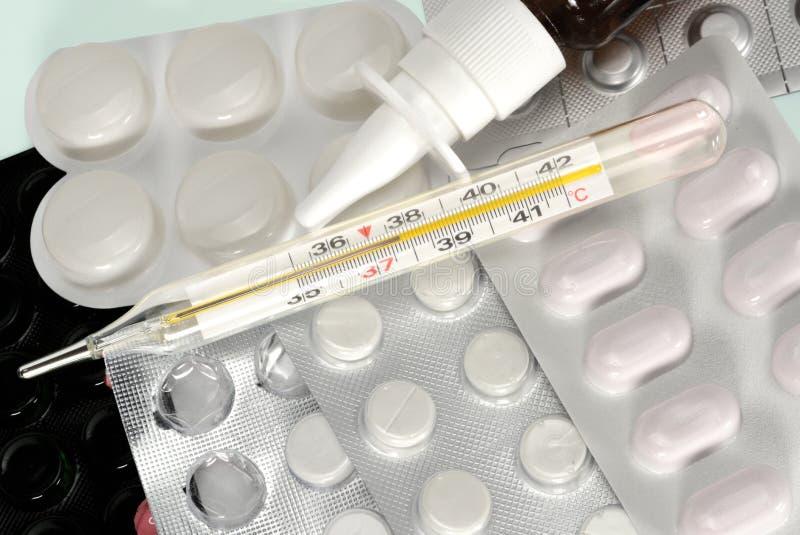 Mercury termometer, nasal sprej och blåsor med piller F?rkylning- och influensabehandlingbegrepp N?ra ?vre makro arkivbild