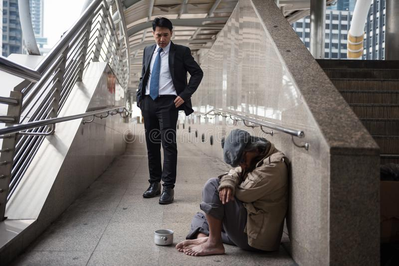 Mercy Businessman look at Homeless in city. Mercy Businessman with black suit look at senior beggar men or old homeless guy at city walk in urban town. Poverty stock image